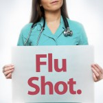 Physician holding a flu shot sign