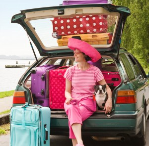Woman and Boston Terrier dog posing with car loaded with colorful suitcases