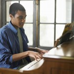 Young man playing piano in house