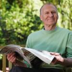 Mature man sitting on garden bench with newspaper, smiling, portrait
