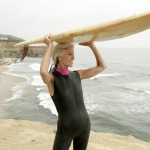 senior woman carrying a surfboard.