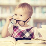 baby girl in glasses reading book