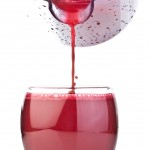 Red fruit juice poured from jug
