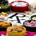 Assortment of pills surrounds a drug prescription