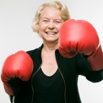 senior woman wearing boxing gloves and throwing punch at viewer.