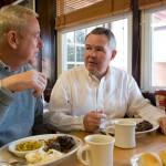 two men eating at a diner