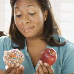 woman looking at donut and apple