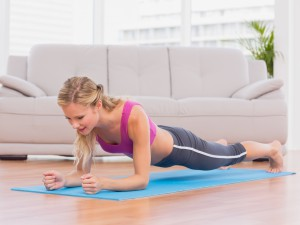 Fit blonde in plank position on exercise mat