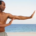man doing martial arts on the beach
