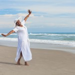 Happy Senior Woman Dancing on Beach