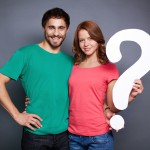 Man and woman holding question mark