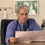 Male doctor seated behind a desk reading