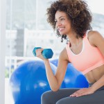 Smiling young woman exercising with dumbbell in gym