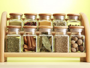 Powder spices in glass jars on wooden shelf
