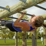 woman doing pull-ups on monkey bars