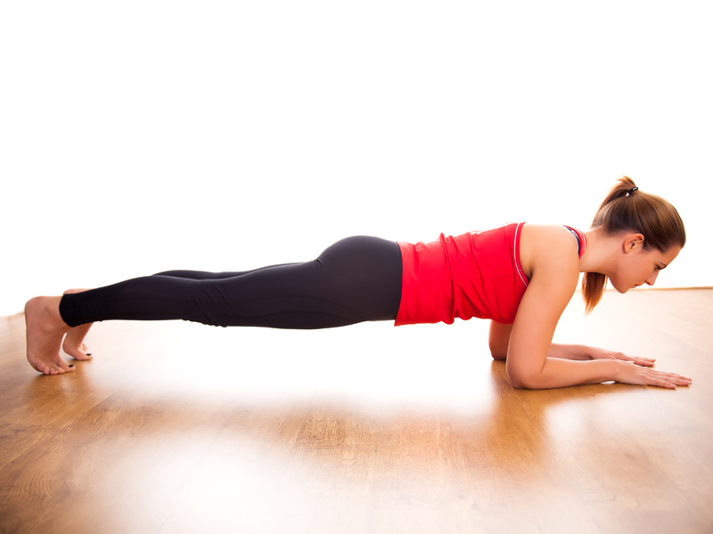 Woman staying away through the isometric exercise: the plank