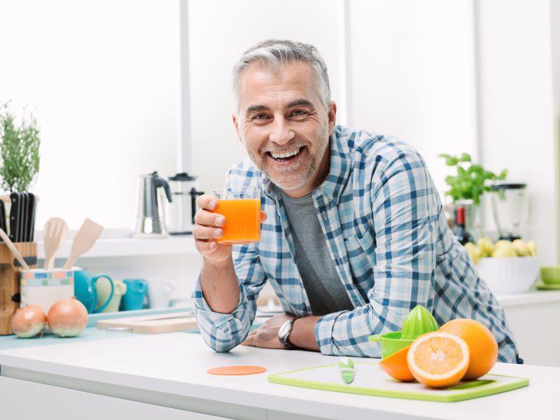man drinking orange juice