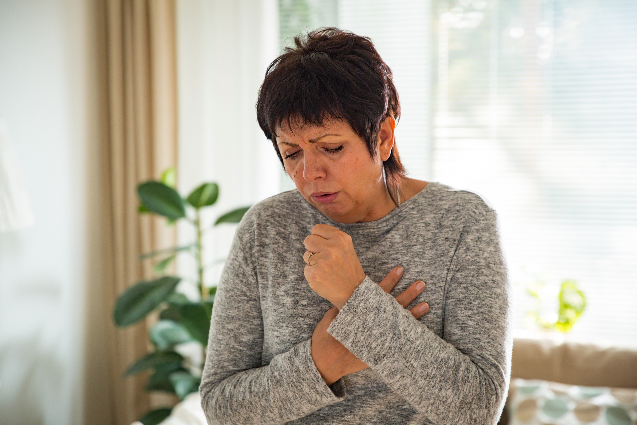 woman coughing, holding chest